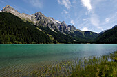 The Antholzer lake in idyllic mountain scenery in the sunlight, Val Pusteria, South Tyrol, Italy, Europe