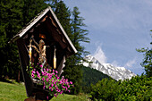 Wayside cross with flowers in front of idyllic mountain scenery, Val Pusteria, South Tyrol, Italy, Europe