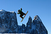 A snowboarder during a jump in front of mountains and blue sky, Dolomites, South Tyrol, Italy, Europe