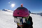 A teenager wearing a helmet and ski goggles in front of sunlit ski slope, South Tyrol, Italy, Europe