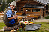 Laughing man sitting in front of an alpine hut, Gostner Schwaige, Alpe di Siusi, South Tyrol, Italy, Europe