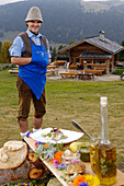 Laughing man and cookout in front of an alpine hut, Alpe di Siusi, South Tyrol, Italy, Europe