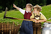 Girl and boy wearing traditional clothes with basket and milk can, Alpine meadow, Agriculture, South Tyrol, Italy
