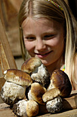 Close up of wild mushrooms, girl in the background. South Tyrolean speciality, Gastronomy, South Tyrol, Italy