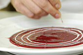 Cook preparing the dessert, raspberry sauce, Gastronomy, South Tyrol, Italy