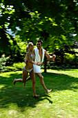 Ein Paar laufen über die Wiese, Bewegung, Park, Südtirol, Italien