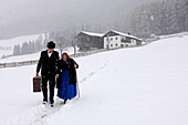 Farmer and mother walking through the snow away from farmhouse, Agriculture, South Tyrol, Italy