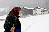 Female farmer walking through the snow, Farmhouse, Agriculture, South Tyrol, Italy