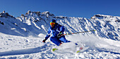 Ski instructor skiing, carving through fresh, powder snow, Mountain landscape in Winter, Seiser Alp, South Tyrol, Italy