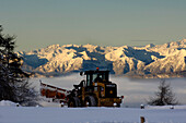 Snow plough clearing snow in the morning light, Seiser Alm, South Tyrol, Italy