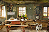 View inside the farmhouse with wooden bench, table and rocking horse, South Tyrolean local history museum at Dietenheim, Puster Valley, South Tyrol, Italy