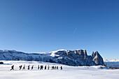 Eine Gruppe Männer laufen durch den Schnee, Seiser Alm, Südtirol, Italien