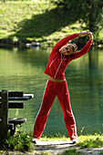 Young woman doing stretching exercises near a lake, Training, Jogging, Fitness, South Tyrol, Italy