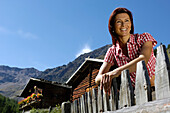 Smiling woman leaning on a wooden fence under blue sky, Mastaun alp, Schnals valley, Val Venosta, South Tyrol, Italy, Europe