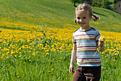 Blond girl on a flower meadow in the mountains, Völs am Schlern, South Tyrol, Italy, Europe