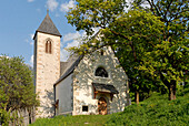 Malerische Kirche unter Bäumen im Sonnenlicht, Völs am Schlern, Südtirol, Italien, Europa