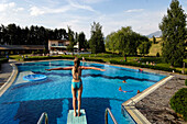 A girl standing on the diving board of the swimming pool at Kastelruth Seis, Telfen, South Tyrol, Italy, Europe