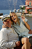 Laughing woman holding a cigar sitting on the lap of a man wearing a captain's cap, Garda lake, Italy, Euorpe