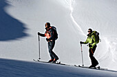 Two cross country skiers at ascent in the sunlight, Schnals valley, Val Venosta, South Tyrol, Italy, Europe