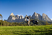 Woman with golf bag on the lawn under blue sky, golf court Kastelruth Alpe di Siusi, Sciliar, South Tyrol, Italy, Europe