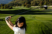 A woman with golf club on the lawn of golf court Kastelruth Alpe di Siusi, Sciliar, South Tyrol, Italy, Europe