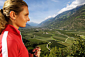 Blond young woman in front of green valley and mountains, Val Venosta, South Tyrol, Italy, Europe
