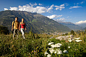 Young couple walking over a meadow in a valley, Naturns, Val Venosta, South Tyrol, Italy, Europe
