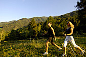 Young couple nordic walking in the sunlight, Val Venosta, South Tyrol, Italy, Europe