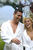 Young couple wearing bathrobes at the garden of a hotel, South Tyrol, Italy, Europe