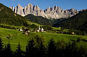 Village of Villnoess with St. Magdalena church, Geislerspsitzen of the Geisler Mountain Range in the background, Villnoess Valley, Dolomites, South Tyrol, Italy