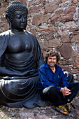 Reinhold Messner sitting in front of a Buddha statue, Extreme Mountaineer and author, MMM, Messner Mountain Museum, South Tyrol, Italy