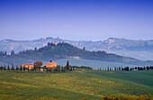 Hügellandschaft mit Landhäusern unter blauem Himmel, Toskana, Italien, Europa