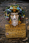 Advertising for wine, ceramic figure and a sign on a wall, Siena, Tuscany, Italy, Europe