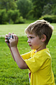 A caucasian boy, 5-10, taking a photograph at a park.