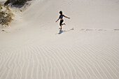 Girl runs, in the sand dunes