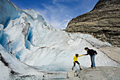 Woman helping another one in Jostedalsbreen glacier (Nigardsbreen). Sogn og Fjordane. Norway.