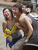 3 Chinese tourists laugh during the wild and wet Songkran Lao New Year Festival, Luang Prabang, Laos