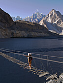 Trekker makes the crossing of the Hunza River in the Karakoram Mountains of Pakistan by rickety footbridge