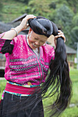 Long Haired Yao woman coiling her hair, a tradition kept by the Red Yao near Guilin, China