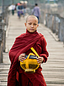 Portrait of a young monk with his alms bowl on the U Bein teak bridge in Myanmar