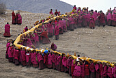 a long line of monks is carrieng a huge Tanka up a maountain in Labrang monastery in Qinghai provice China