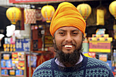A friendly Sikh man smiles to the camera
