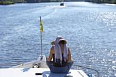 Woman reading on a boat, river Havel near Ketzin, Brandenburg, Germany
