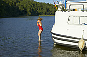 Woman jumping into lake Lankensee from a houseboat, Brandenburg, Germany