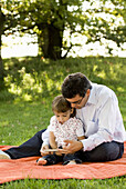 Father and daughter (2-3 years) reading a book, English Garden, Munich, Bavaria, Germay