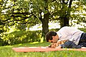 Vater küsst Tochter auf die Wange, Englischer Garten, München, Bayern, Deutschland
