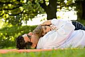 Vater und Tochter liegen auf einer Wiese, Englischer Garten, München, Bayern, Deutschland
