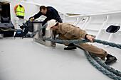 Zwei Besatzungsmitglieder an Bord der Yacht Hanse Explorer befestigen ein Tau auf einer Reise rund um die Shetlandinseln, Schottland, Grossbritannien