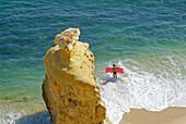 View at beach and a woman with air mattress on the waterfront, Praia da Marinha, Algarve, Portugal, Europe