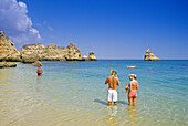 People standing in the water ready to snorkel, Praia de Dona Ana, Algarve, Portugal, Europe